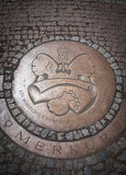 下水道的圆铁舱口盖在鹅卵石路面 免版税库存照片