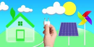 不伤环境的拿着插座的房子和手连接了到一些太阳电池板和风车 库存图片