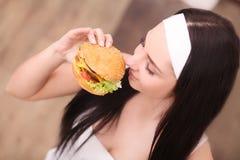 不健康吃 背景汉堡干酪鸡概念黄瓜深鱼食物油煎了旧货莴苣木三明治的蕃茄 拿着汉堡和摆在木背景的时兴的少妇画象  关闭 图库摄影