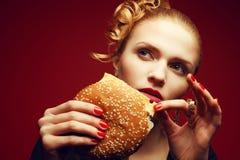 不健康吃 背景汉堡干酪鸡概念黄瓜深鱼食物油煎了旧货莴苣木三明治的蕃茄 吃汉堡的妇女画象 库存照片