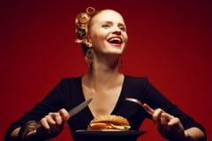 不健康吃 背景汉堡干酪鸡概念黄瓜深鱼食物油煎了旧货莴苣木三明治的蕃茄 一个愉快的金发碧眼的女人的画象 免版税库存照片