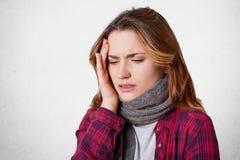 不健康的不适的妇女感觉可怕的头疼,保留在头的手,穿温暖的被编织的围巾,并且便衣,神色绝望地做 免版税库存图片