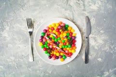 不健康的甜食物概念用在白色的五颜六色的糖果制地图 免版税库存图片
