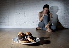 不健康的糖油炸圈饼和松饼和被诱惑的少妇或者te 免版税库存图片