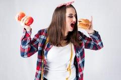不健康的食物肥胖妇女概念,饥饿的女孩XXL吃坏食物, 免版税库存照片