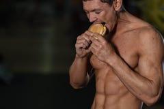 不健康的饮食概念,运动员吃汉堡包 库存图片
