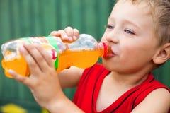 不健康被装瓶的男孩饮用的碳酸钠 免版税库存图片