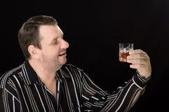 不剃须的人看玻璃白兰地酒 图库摄影