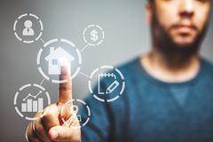 不动产概念,财产价值图,与一个人在接触按钮的背景中,买房子 免版税库存照片