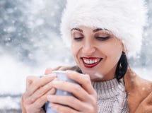 不可思议的冬天片刻-与杯子的妇女画象在sno的热的茶 图库摄影