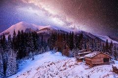 不可思议的冬天积雪的树和山村 33c 1月横向俄国温度ural冬天 与星和星云的充满活力的夜空和 免版税库存图片