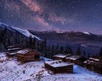 不可思议的冬天积雪的树和山村 33c 1月横向俄国温度ural冬天 与星和星云的充满活力的夜空和 库存照片