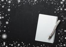 不可思议的圣诞节题材背景、雪花、木铅笔和一封空的信件在黑桌上 免版税库存图片