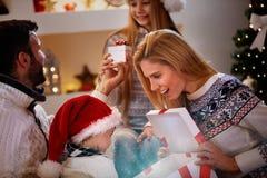 不可思议的圣诞节-享用在圣诞节礼物的家庭 图库摄影