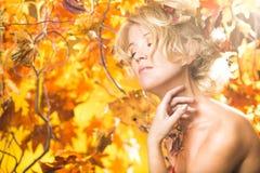 不可思议的在叶子的金子秋天白肤金发的女孩画象 免版税库存图片