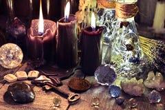 不可思议的水晶、礼节对象、诗歌、黑蜡烛和瓶在巫婆桌上 免版税图库摄影