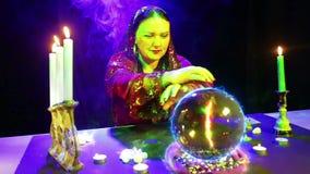 不可思议的沙龙的吉普赛人参与与一个水晶球的魔术,火标志欧元出现 股票视频