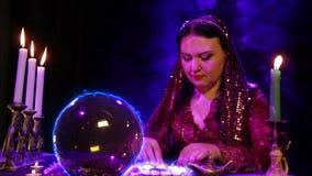 不可思议的沙龙的吉普赛人参与与一个水晶球的魔术,电辉光和火石头 影视素材