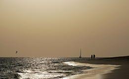 不可思议的海洋 海洋 在日落前的明亮的光 波浪 风 人们 风帆 海滩 强光 免版税库存照片