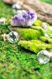 不可思议的烧瓶和紫色的石头在鲜绿色青苔在森林万圣夜题材 巫术和草药医术学 免版税库存图片