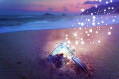 不可思议的瓶子开放在海滩在发布星团创造性的概念的晚上 库存照片