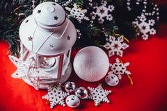 不可思议的白色灯笼站立与对此的白色编织星和杉树分支和在圣诞节红色背景的一个雪球 免版税库存照片