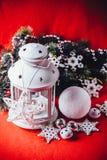 不可思议的白色灯笼站立与对此的白色编织星和杉树分支和在圣诞节红色背景的一个雪球 图库摄影