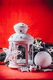 不可思议的白色灯笼站立与对此的白色编织星和杉树分支和在圣诞节红色背景的一个雪球 免版税库存图片