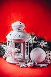 不可思议的白色灯笼站立与对此的白色编织星和杉树分支和在圣诞节红色背景的一个雪球 免版税图库摄影