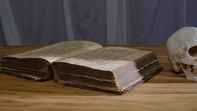 不可思议的礼拜式 古老书和人的头骨 概念为万圣夜 股票录像