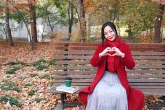 不可思议的秋天、愉快秋天的妇女和极乐,美丽的妇女坐一条长凳在秋天公园 免版税库存图片