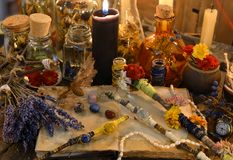 不可思议的鞭子、开放日志书、淡紫色花和黑蜡烛在巫婆桌上 图库摄影