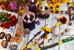 不可思议的鞭子、黑蜡烛、花和飞蛾-死亡标志,在巫婆桌上 免版税库存照片