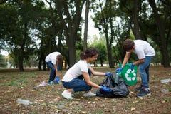 不同的人合作与回收项目,拾起在公园志愿者社区服务的垃圾 免版税库存照片