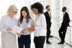 不同的公司雇员有偶然谈话在公司走廊 免版税库存照片