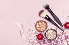 不同的化妆构成刷子,脸红粉末球,圣诞节球,以星的形式全息照相的闪烁五彩纸屑在桃红色 免版税库存图片