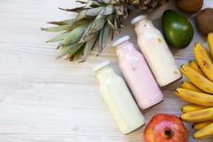 不同的口味果子圆滑的人在玻璃瓶子的有在白色木背景的成份的 顶视图,从上面 平的位置 库存照片