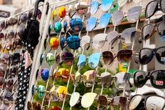不同的品牌和颜色太阳镜在商店窗口 美丽的太阳镜 免版税图库摄影