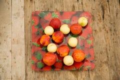 不同的品种油桃在一块板材的用草莓 免版税库存图片