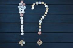 不同的国家疏散硬币以一个问号和感叹号的形式在木桌上 r 免版税库存照片