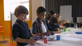 不同的孩子在幼儿园递绘画