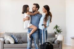不同的家庭身分在有手提箱行李的客厅 图库摄影