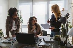 不同的小组微笑的女商人有断裂在办公室谈话 免版税库存照片
