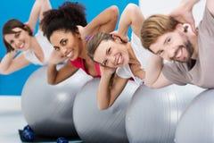 不同的小组朋友获得乐趣在健身房 免版税库存图片