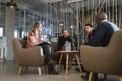 不同的小组青年人开会议在大厅 免版税库存图片