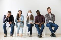 不同的工作候选人乏味,当等待采访时 免版税库存照片