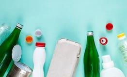 不同的废物平的位置准备好回收在绿色背景 塑料,玻璃,纸,锡罐 库存照片