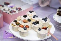 不同的开胃果子馅饼、蛋糕篮子与白色奶油和新鲜的多彩多姿的莓果,新鲜的夏天点心 库存照片