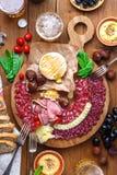 不同的快餐和开胃菜的混合:香肠、面包、橄榄、乳酪、栗子、豌豆和啤酒在木板 顶层 库存照片