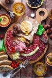 不同的快餐和开胃菜的混合:香肠、面包、橄榄、乳酪、栗子、豌豆和啤酒在木板 顶层 免版税图库摄影